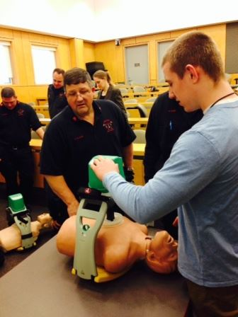 Andover High School Senior Max Grant learns how to operate an automatic chest compression device dur